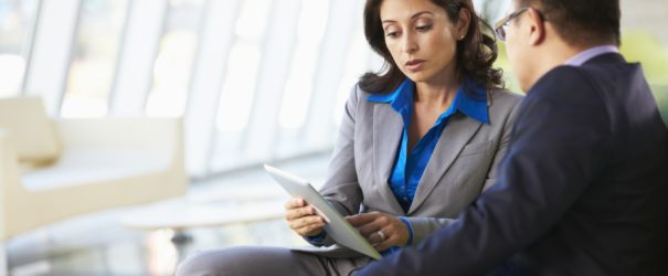 businesspeople-with-digital-tablet-in-meeting-min